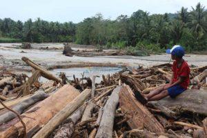 Seorang anak di Desa Tuva Kecamatan Gumbasa Kabupaten Sigi, Sulawesi Tengah duduk diatas sisa kayu gelondongan yang hanyut dibawa sungai saat banjir bandang.(Foto:Abdee Mari/KabarSelebes.id)